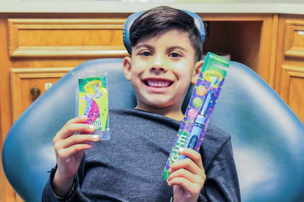 Bellmead Kids Dentistry pediatric patient in the dentist chair showing off the free promotional gifts he received