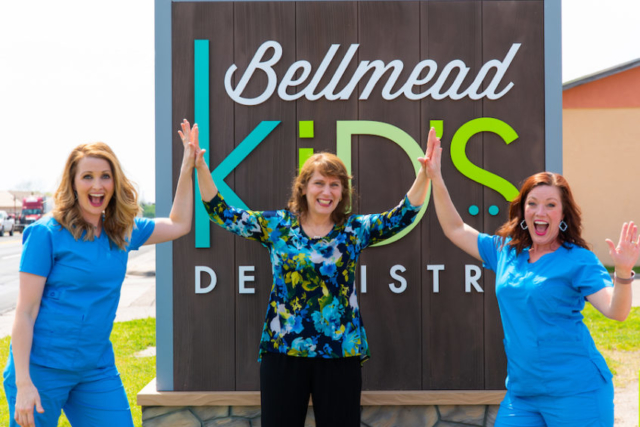 Dr. Francis and two team members in front of bellmead smiles sign
