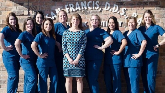 Bellmead Kids Dentistry Dr. Susan Francis wearing a blue print dress with all the office team members wearing blue uniform standing for a photo shoot outside the office in front of the office name on the brick wall