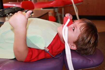 Bellmead Kids Dentistry patient in the treatment room with a sedation mask on his nose showing the thumb up signal