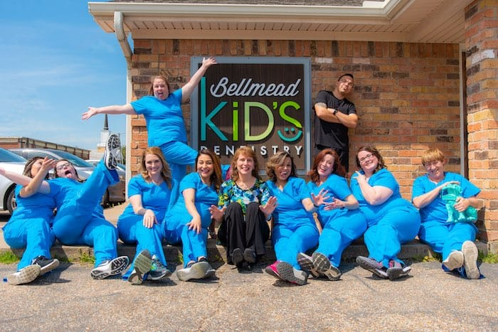 Bellmead Kids Dentistry Dr. Susan Francis with all the office team members wearing blue uniform standing for a photo shoot outside the office in front of the office name on the brick wall